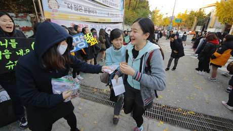 Alunos mais novos vão para as escolas incentivar os que estão prestando a prova, cantando e distribuindo doces a eles