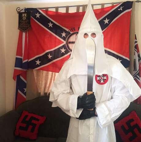 Thomas segura um facão vestido com o traje característico da Ku Klux Klan