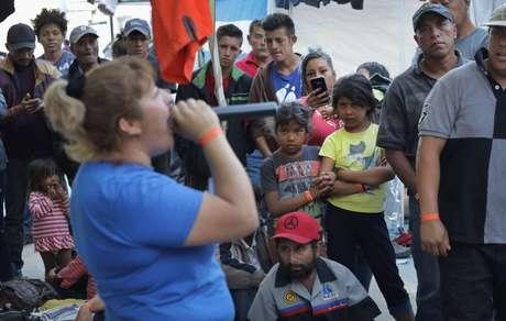 Um grupo de migrantes observa uma mulher cantando no karaokê no abrigo improvisado