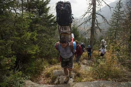 Enquanto você 'morre' para subir a montanha, um sherpa carregado de malas passa correndo como se não fosse nada