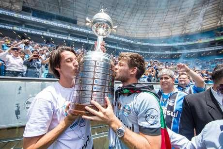 Os gremistas Pedro Geromel e Kannemann beijam a taça da Libertadores conquistada em 2017