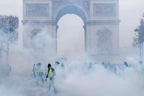 Manifestantes com coletes amarelos protestem em frente ao Arco do Triunfo, em Paris, em meio a bombas de gás lacrimogêneo 01/12/2018 REUTERS/Stephane Mahe