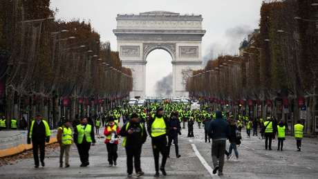 Manifestantes vestidos com coletes amarelos - peça de segurança obrigatória nos carros franceses - protestam em frente ao Arco do Triunfo
