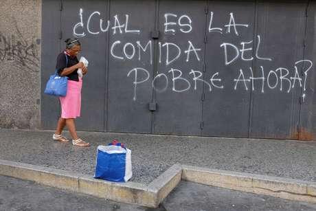 Mulher anda em frente a pichação de protesto em Caracas