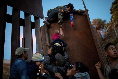 Imigrantes de Honduras que fazem parte de caravana a caminho dos EUA pulam cerca na fronteira do México com os EUA na cidade mexicana de Tijuana 03/12/2018  REUTERS/Alkis Konstantinidis
