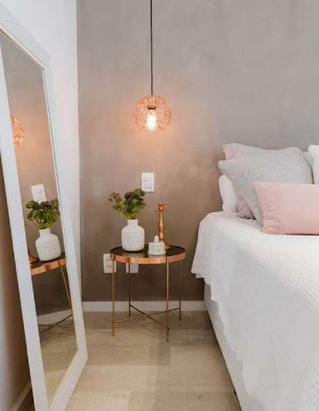 20. Decoração de quarto moderno com parede de cimento queimado, espelho apoiado no piso e mesa lateral com pendente rose gold – Foto: Pinterest