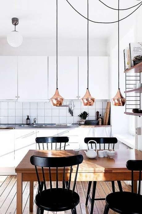 25. Decoração com pendente rose para cozinha com mesa de madeira e cadeiras pretas – Foto: Dekorama