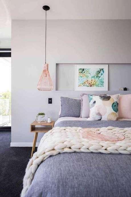 33. Decoração minimalista para quarto rose gold com luminária moderna ao lado da cama – Foto: Pluska