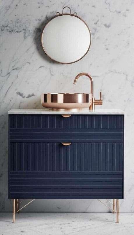 42. A gabinete azul marinho deu um toque super moderno e sofisticado para o banheiro com detalhes em rosa metalizado – Foto: iFuun