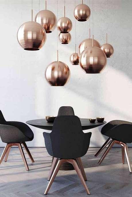48. Decoração rose gold para sala de jantar com cadeiras modernas e pendentes redondos sobre a mesa de jantar – Foto: Behance
