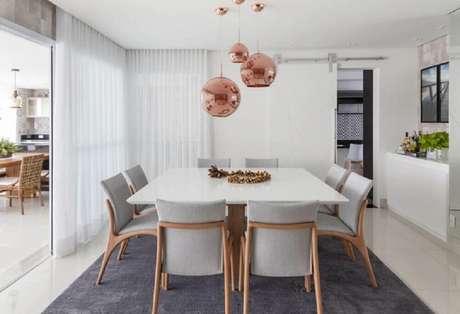 50. Decoração rose gold sala de jantar com mesa quadrada toda branca e pendentes redondos – Foto: Foto Érica Salguero