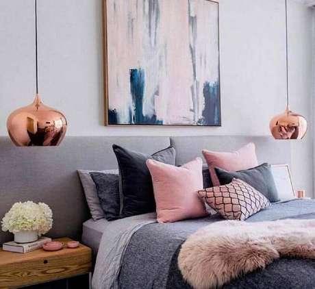 66. Decoração para quarto rose gold e cinza com grande quadro na cabeceira e pendentes nas laterais da cama – Foto: FirePont