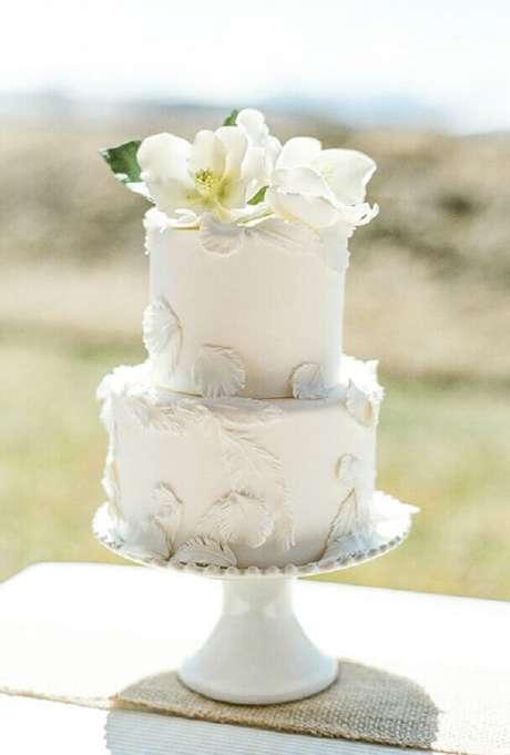 18. Bolo de casamento simples e bonito 2 andares e todo branco decorado com flores brancas no topo – Foto: Decobake