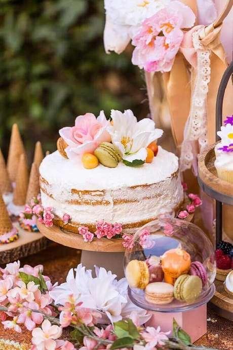 44. Decoração romântica com bolo de casamento simples com chantilly e flores – Foto: Brit + Co