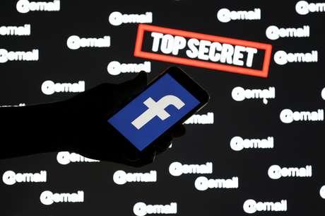 """Uma pessoa segura um smartphone com o logotipo do Facebook na frente das palavras exibidas """"ultra secreto"""" e """"email"""" 6/12/ 2018. REUTERS/Dado Ruvic"""