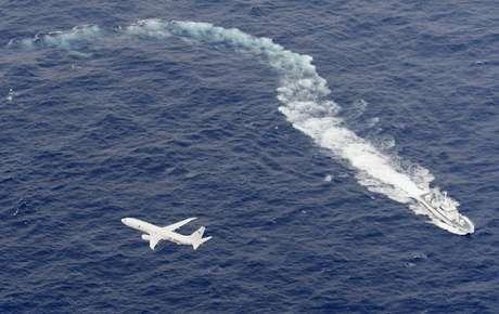 Navio de patrulha da Guarda Costeira japonesa e avião da Marinha dos EUA durante operação de busca a fuzileiros desaparecidos 06/12/2018 Kyodo via Reuters