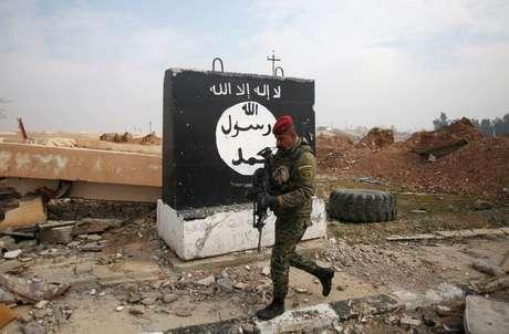 Soldado iraquiano passa por painel pintado com bandeira preta do Estado Islâmico em Mosul 21/01/2017  REUTERS/Khalid al Mousily