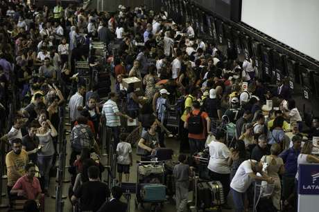Passageiros formam fila no check-in da LATAM do Aeroporto de Guarulhos na tarde deste sábado (15); passageiros relatam problemas com cancelamentos
