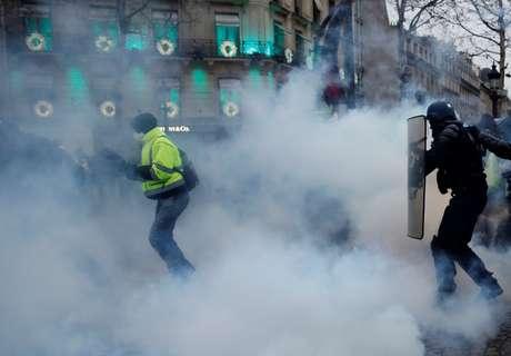 Manifestante corre em Paris enquanto polícia joga gás lacrimogênio para dispersar ato