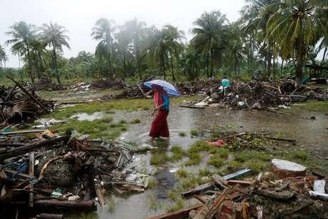 Mulher anda entre os escombros deixados pelo tsunami na Indonésia