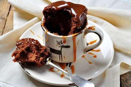 Bolo de caneca de chocolate com bastante calda