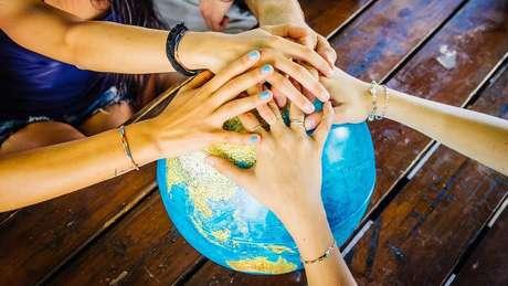 Várias mãos sobre esfera que representa o planeta Terra