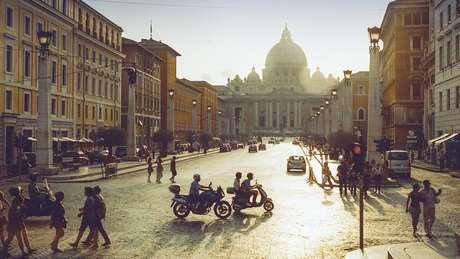 Vista geral do Vaticano no pôr do sol, com pessoas e motos em primeiro plano