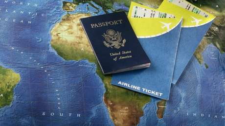 Passaporte americano e tickets de voo sobre mapa mundial
