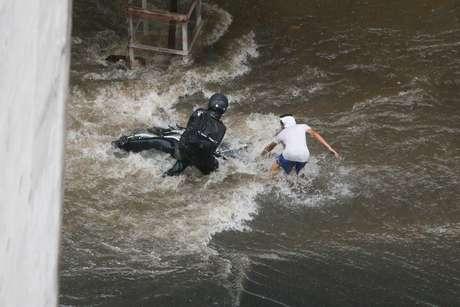 Pedestre ajuda motociclista arrastado pelas águas da chuva na Avenida Nove de Julho, no centro da capital paulista