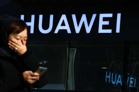 Uma mulher confere seu telefone celular em frente a uma loja da Huawei na China. 19/12/2018.  REUTERS/Thomas Peter
