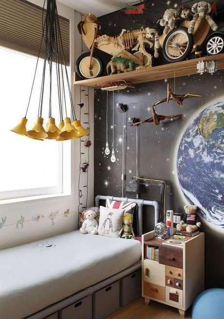 47. Decoração de quarto jovem com papel de parede imitando espaço, pendente minimalista amarelo e caixas organizadoras embaixo da cama – Foto: André Piva