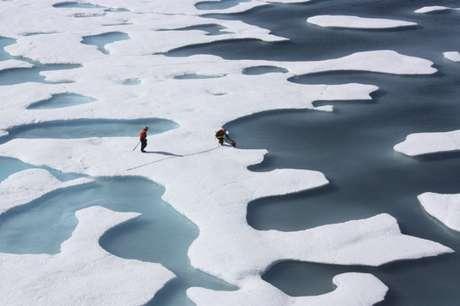 A tripulação da Guarda Costeira dos EUA recupera suprimentos lançados por paraquedas no Oceano Ártico12/07/ 2011 Kathryn Hansen/NASA via REUTERS