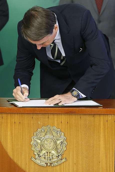 O presidente Jair Bolsonaro (PSL) assina o decreto da flexibilização de compra de arma de fogo e munição no País