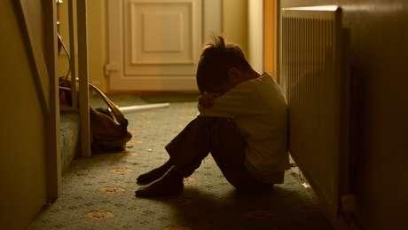 Foto ilustrativa sobre abuso infantil - menino chora sentado no corredor de casa