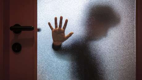 Foto ilustrativa sobre abuso infantil - menino visto através de porta de vidro fosco