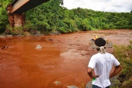 Indígena observa o rio Paraopeba tomado pela lama