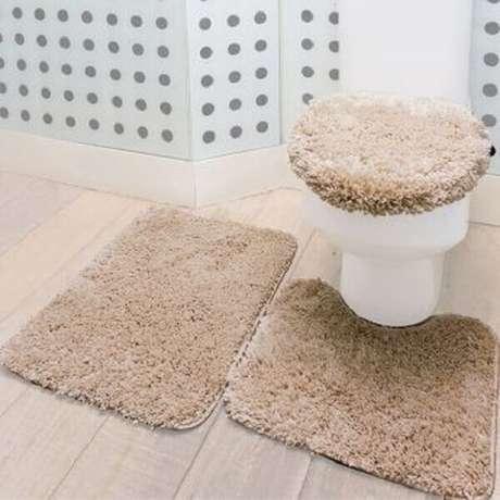 38- O jogo de tapete para banheiro felpudo tem a cor bege que combina com o piso amadeirado. Fonte: Pinterest