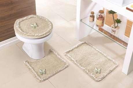 19- O jogo de tapete para banheiro tem três peças e aplicação de borboleta. Fonte: Magazine Luiza