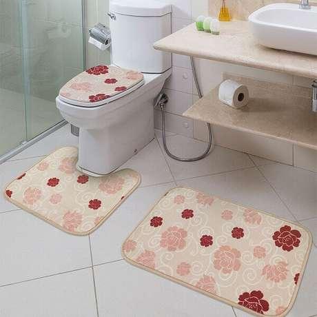 37- O fundo do conjunto de tapete para banheiro tem o mesmo tom da bancada de mármore Travertino. Fonte: Toalha de mesa bordada