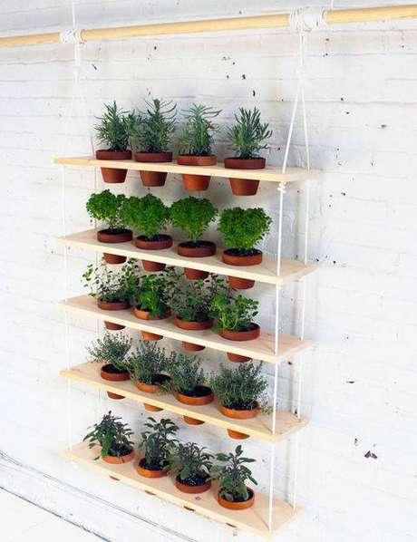 1. Esse tipo de horta vertical suspensa feita com madeira e vasos de barro, por exemplo, pode ser feita por você mesmo