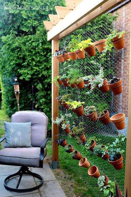 12. Área aberta com horta vertical com vasos de barro suspensos em telado