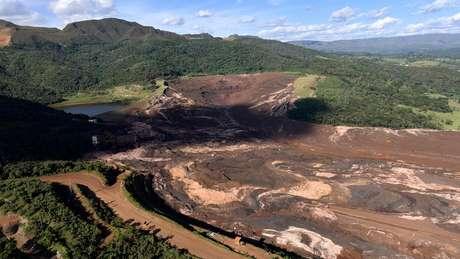 """Visão da barragem da mina Córrego de Feijão após o rompimento; a estrada onde estava o caminhão de Ana Paula fica à direita do entroncamento em """"v"""", tomada parcialmente pela lama"""