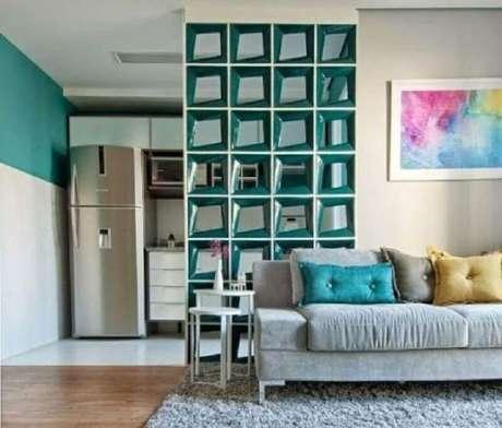 18. Aqui a decoração da sala ganhou uma divisória de cobogó cerâmico da mesma cor da parede da cozinha – Foto: Bose Bento