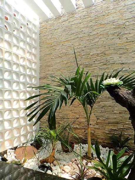 42. Decoração para jardim de inverno com revestimento de pedra canjiquinha e parede de cobogó cerâmico branco – Foto: Webcomunica