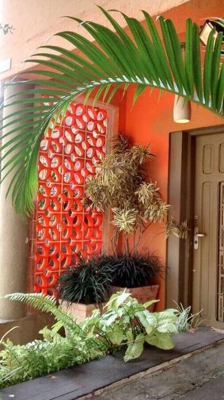52. Decoração de varanda com cobogó pintado de vermelho e várias plantas – Foto: Pinterest