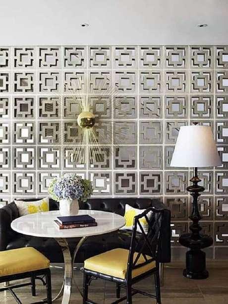 56. Parede de cobogó de cimento para decoração de sala com sofá preto – Foto: Greg Natale