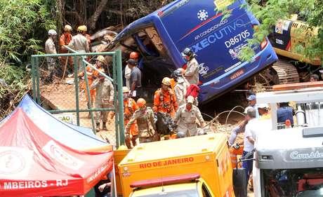 Bombeiros retiram um corpo do ônibus que foi soterrado na Avenida Niemeyer após deslizamento na Favela do Vidigal, na Zona Sul do Rio, durante forte chuva na noite de quarta-feira (07/02/2019)
