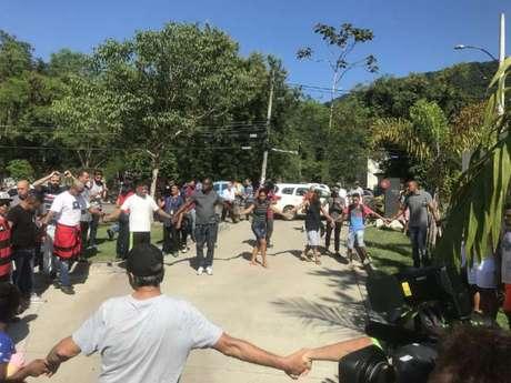 Pessoas fazem corrente de oração na frente do Ninho do Urubu (Foto: Matheus Dantas)