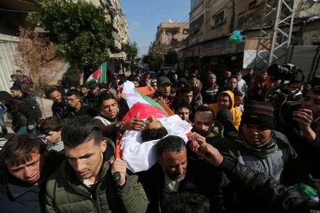 Corpo do adolescente palestino Hassan Shalabi, 14, morto durante protesto na fronteira entre Israel e Gaza, é carregado durante funeral na região central de Gaza.