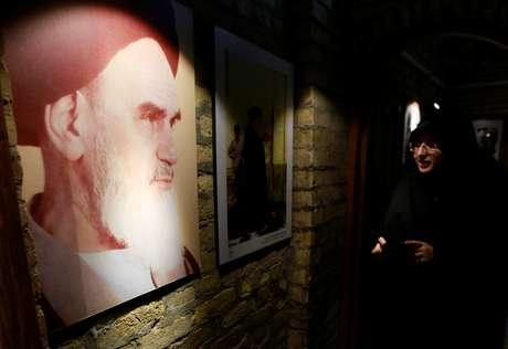 Mulher olha para imagem do aiatolá Ruhollah Khomeini, um dos líderes da revolução de 1979